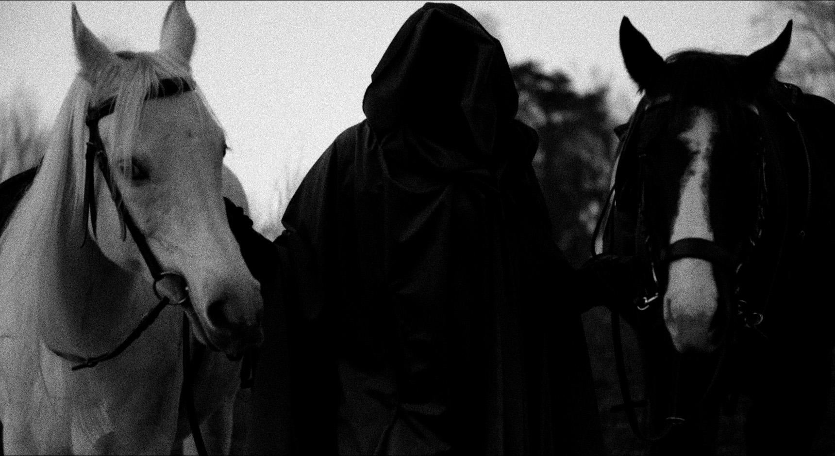 Bilde fra musikkvideoen - person med hette går med to hester