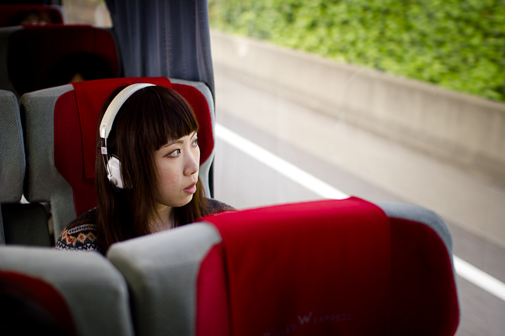 Aiko som sitter på en buss med hodetelefoner og ser utover