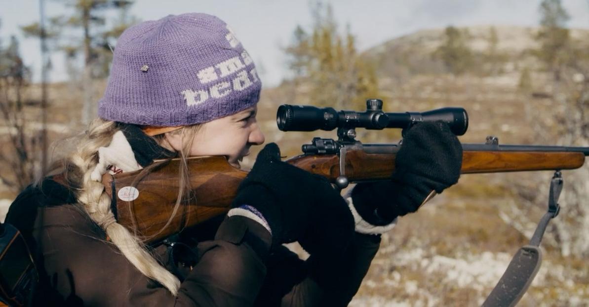 Sigrid holder et gevær, klar til å skyte, ute i skogen